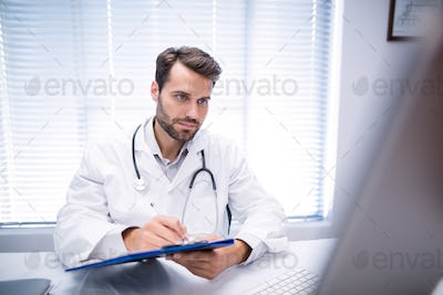 Male doctor writing on clipboard while working on personal computer