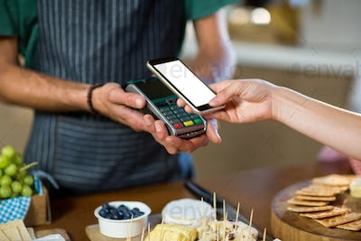 Mid section of woman paying through nfc technology at counter