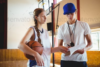 Female basketball player discussing with male coach