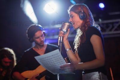 Singer wearing headphones while singing at nightclub