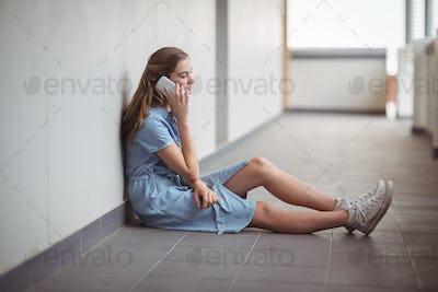 Schoolgirl talking on mobile phone in corridor
