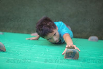 Boy reaching climbing holds on wall