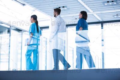 Doctor with nurses walking in corridor