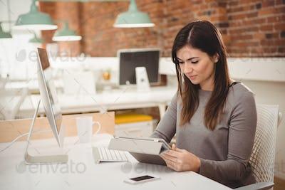 Female executive using digital tablet at desk