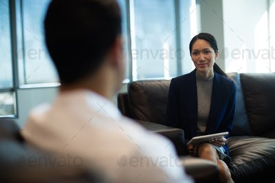 Businesswoman discussing with male colleague while holding digital tablet