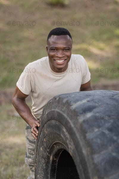 Portrait of happy military soldiers exercising with tyre