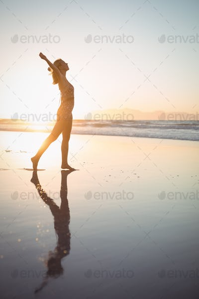 Side view of carefree woman with arms outstretched at beach
