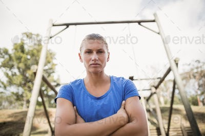 Portrait of fit woman standing with arms crossed during obstacle course