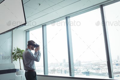 Businessman using virtual reality glasses while standing at office