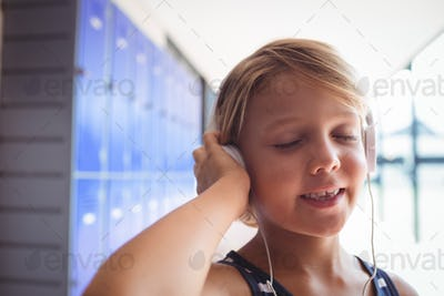 Elementary student with eyes closed listening music through headphones