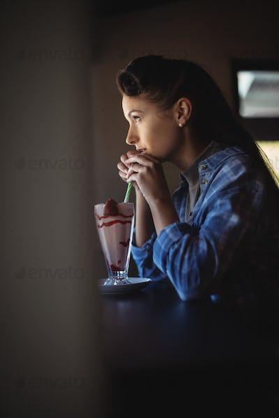 Thoughtful woman having milkshake
