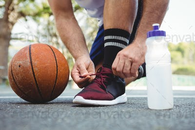 Low section of basketball player tying shoelace