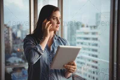 Woman talking on mobile while holding tablet