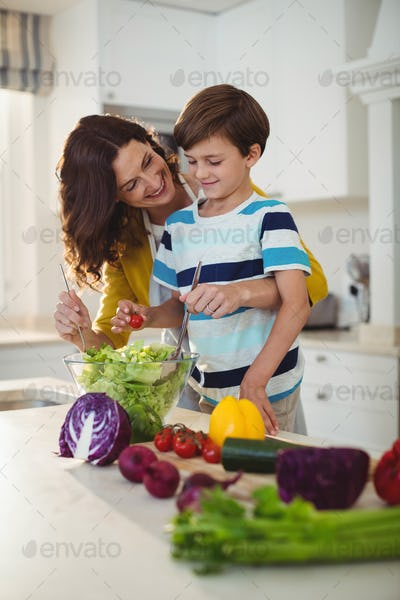 Mother and son mixing the salad in kitchen