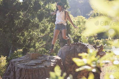 Female hiker jumping from tree stumps in forest