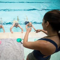 Young trainer assisting senior swimmers at poolside