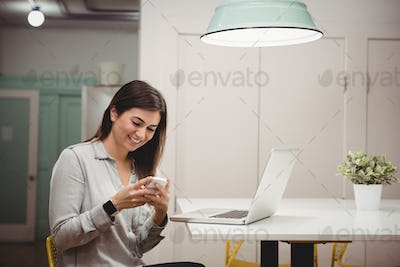 Smiling executive using mobile phone