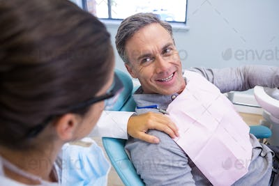 Patient looking at dentist while sitting on chair in clinic