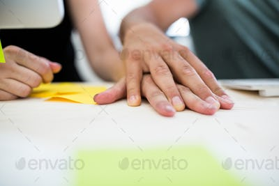 Close-up of office colleagues with hand on hand at desk
