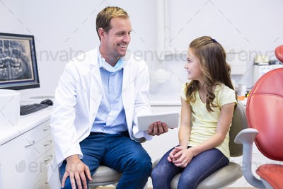 Dentist interacting with young patient in dental clinic