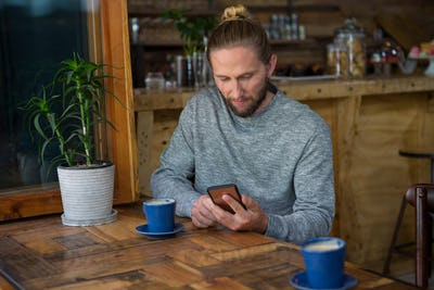 Male hipster using mobile phone at table in coffee shop
