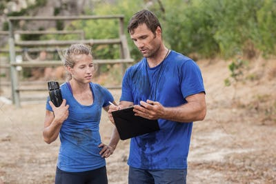 Trainer and woman discussing over clipboard during obstacle course