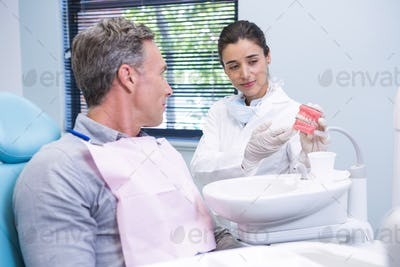 Happy dentist showing dental mold to man