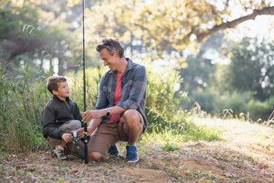 Father and son looking at each other while holding fishing rod