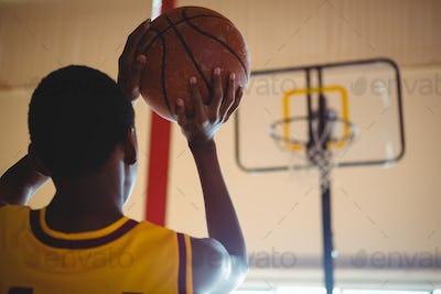 Rear view of teenage boy playing basketball