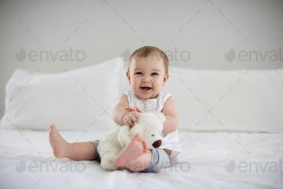 Cute baby girl playing with soft toy on bed