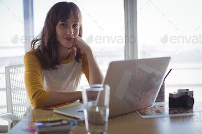 Portrait of young businesswoman sitting at office desk