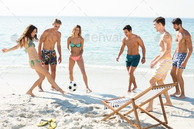 Happy friends playing soccer on shore at beach