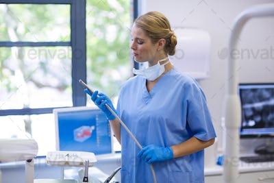 Female nurse holding dental tool