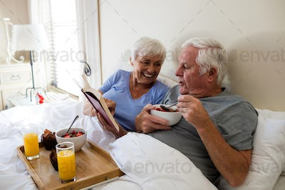 Senior couple reading a book while having breakfast in the bedroom