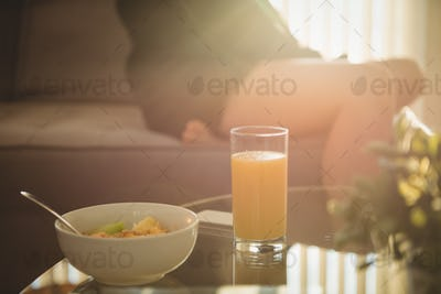 Close up of breakfast on table while woman sitting on sofa