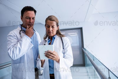 Male and female doctor discussing over digital tablet