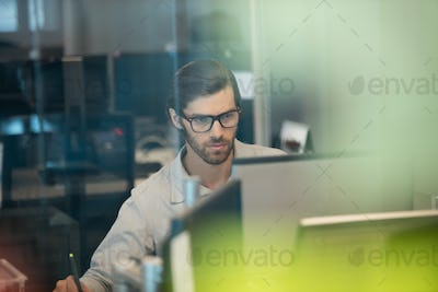 Concentrated businessman working on computer at office