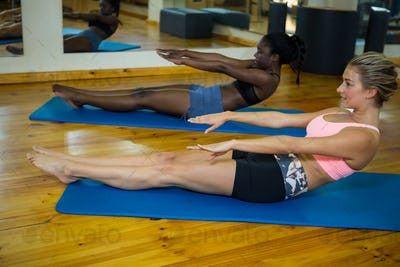 Two fit women doing stretching exercise on mat
