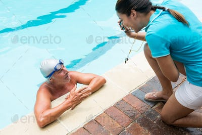 Coach showing stopwatch to senior man