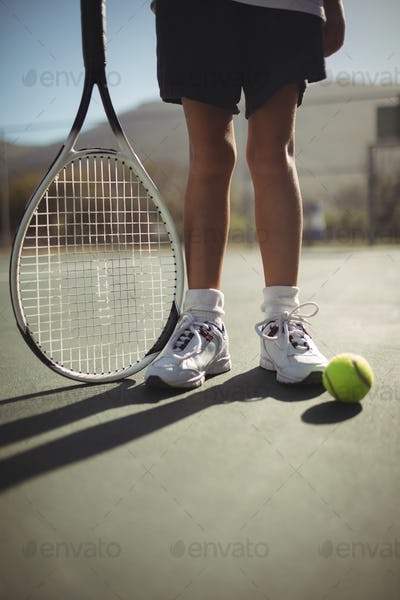Girl with tennis racket and ball on court