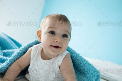 Cute baby girl smiling on bed