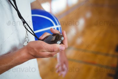 Midsection of basketball coach with stopwatch