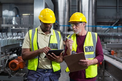 Two factory workers with clipboard and digital tablet working in the plant