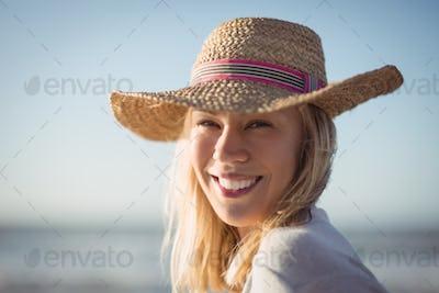 Portrait of happy woman wearing sun hat at beach