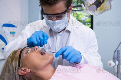 Close up of dentist examining woman