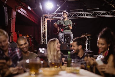 Smiling friends sitting at table with musician in background