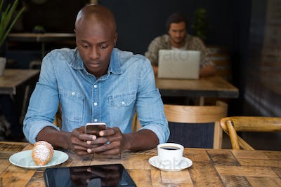 Man using mobile phone at wooden table in coffee shop