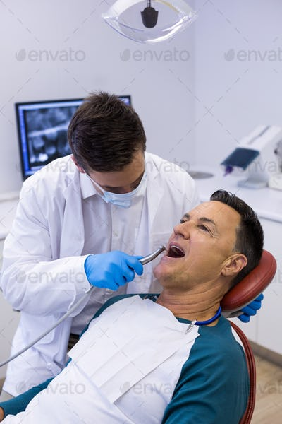 Dentist examining a male patient with tools