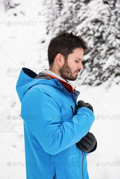 Skier zipping his jacket on snowy mountains