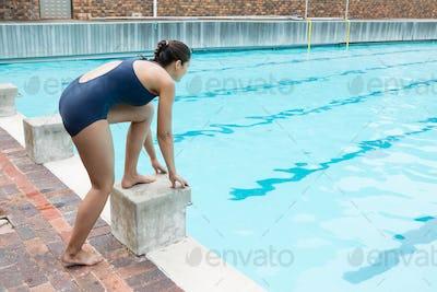 Female swimmer preparing to dive in pool